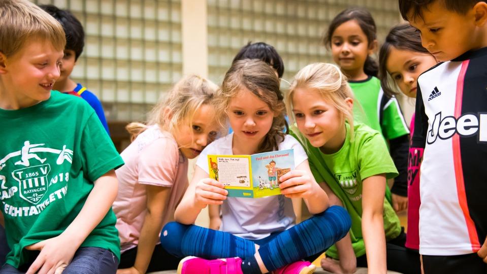 Eine Gruppe vo Grundschulkindern schauen sich ein Pixi-Buch an. Im Hintergrund sieht man die Glaskachelwand der Sporthalle.