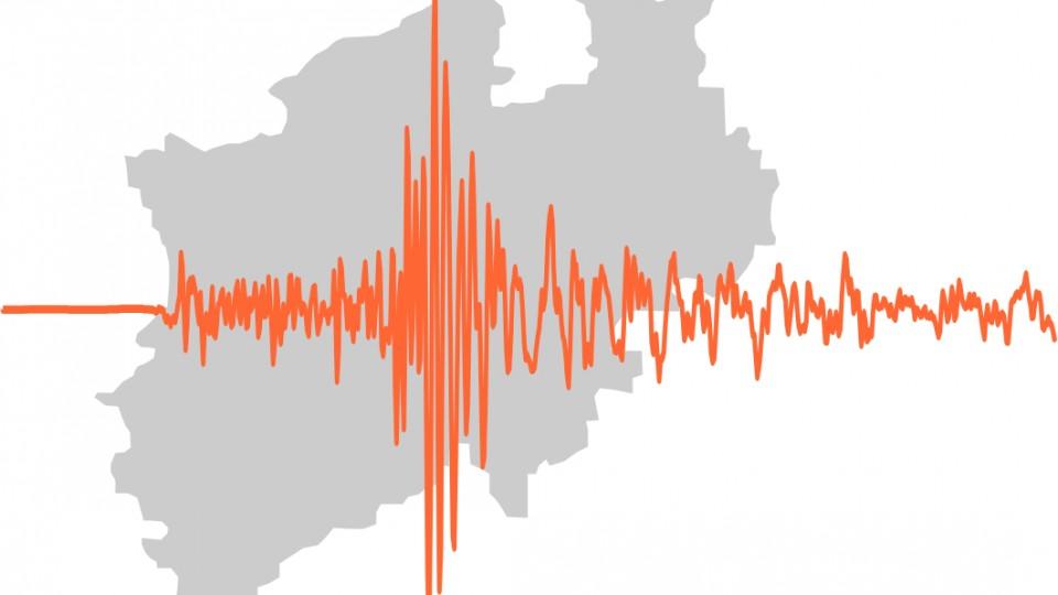 Die Grafik zeigt das Logo des neuen Erdbebenalarmsystems: Eine graue Reliefkarte von NRW im Hintergrund, davor eine orangefarbene Amplitude.