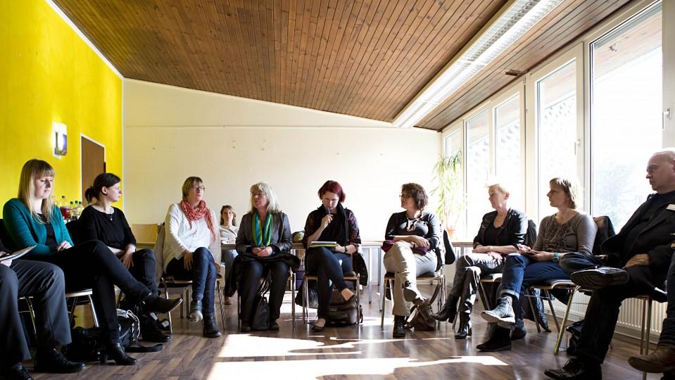 Das Foto zeigt einen Stuhlkreis mit mehren Menschen, die miteinander diskutieren.