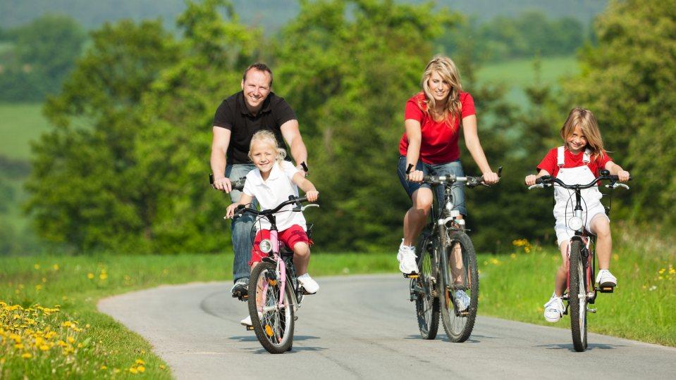 Eine Familie fährt mit Fahrrädern über einen Asphaltweg zwischen grünen Wiesen und Büschen.