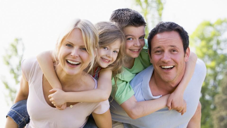 Auf dem Bild sind eine Mutter und ein Vater zu erkennen, die jeweils ein kleines Mädchen und einen kleinen Jungen auf ihren Schultern tragen.