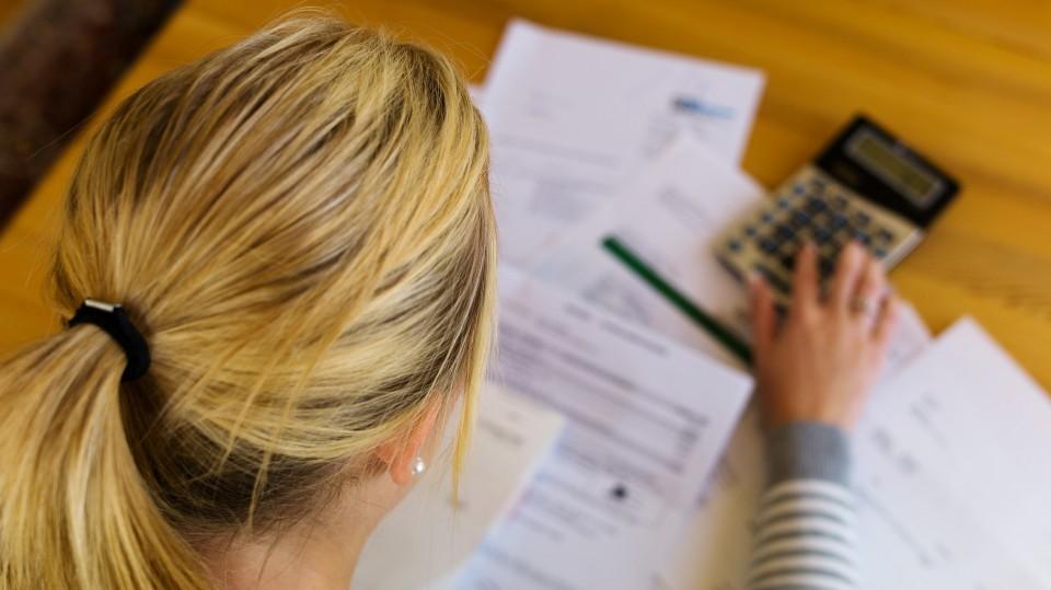 Das Foto zeigt eine Frau, die am Schreibtisch mit Taschenrechner und Formularen arbeitet.