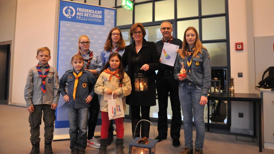 Auf dem Foto ist Ministerin Ute Schäfer gemeinsam mit Kindern und Jugendlichen zu sehen, die das Friedenslicht aus Betlehem überreichen.