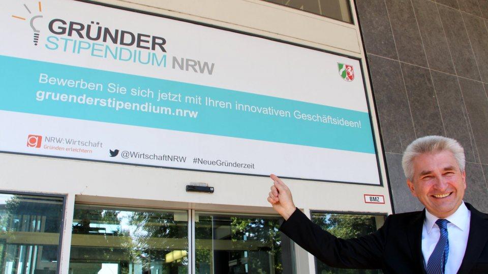 Wirtschaftsminister Pinkwart rechts unten im Bild zeigt lächelnd auf das Gründerstipendium NRW.
