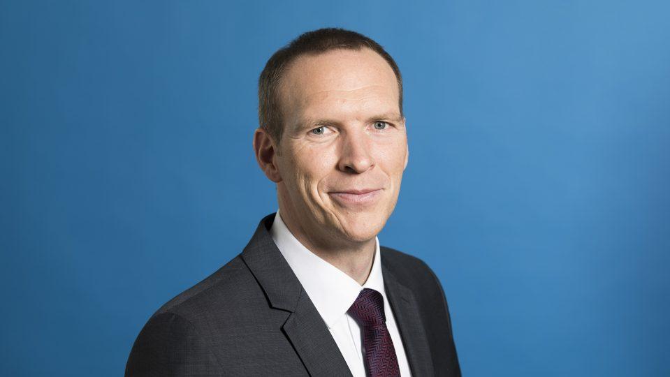 Staatssekretär Heinisch freundlich lächelnd - Hintergrund blau.