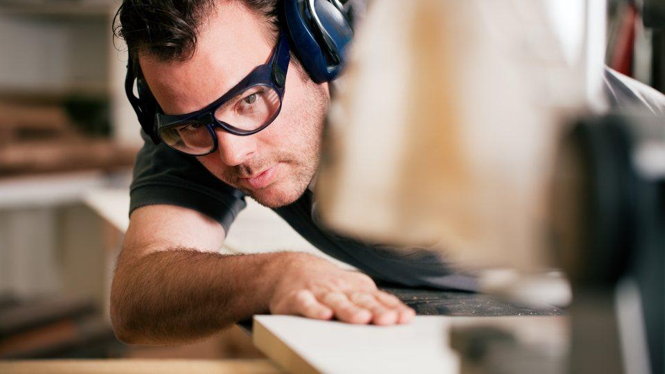Ein Mann im schwarzen T-Shirt mit schwarzer Brille und Kopfhörern als Lärmschutz sägt ein Holzbrett an einer Maschine.