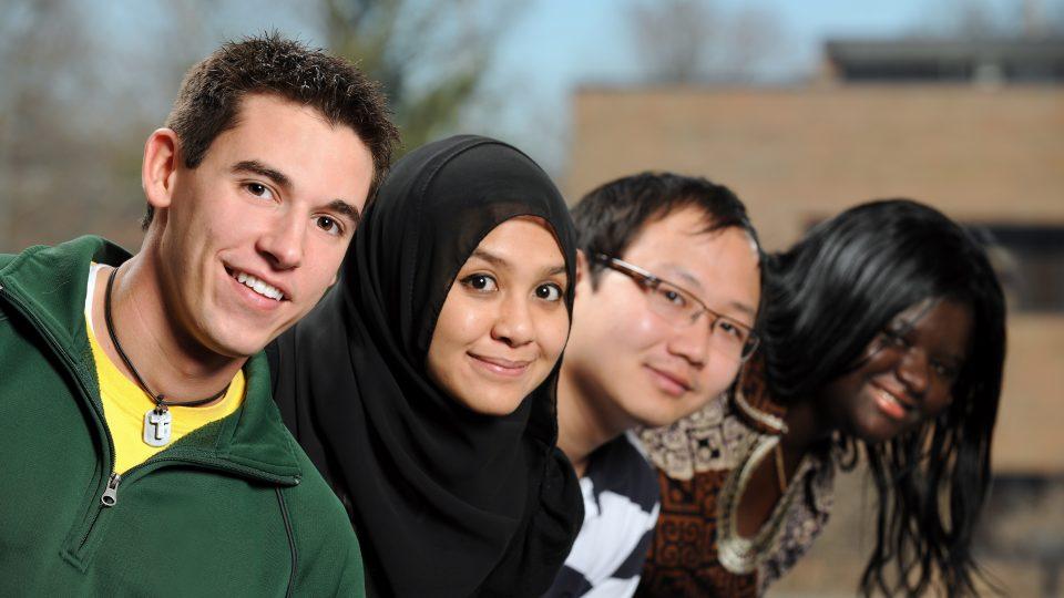 4 lächelnde Menschen unterschiedlicher Herkunft