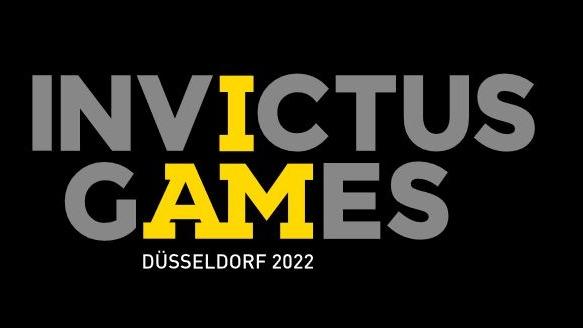 """Der Schriftzug """"Invictus Games"""" in hellgrauen Großbuchstaben auf schwarzem Grund. Das zweite """"I"""" und daas """"AM"""" sind gelb, so das es heißt """"I am invictus games""""."""