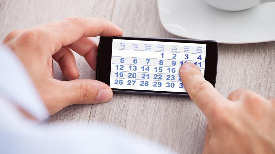 Eine Hand hält ein Smartphone mit einem Kalender auf dem Bildschirm, mit einem Zeigefinder auf dem Display