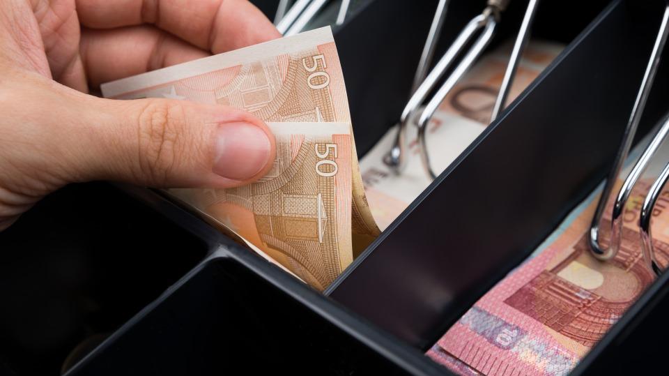 Jemand nimmt mit seiner linken Hand einen 50 Euro-Schein aus einer Kasse.
