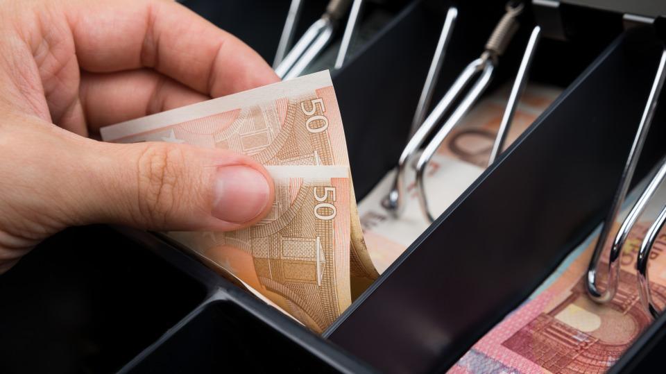 Eine Hand zieht Geldscheine aus einer Kasse
