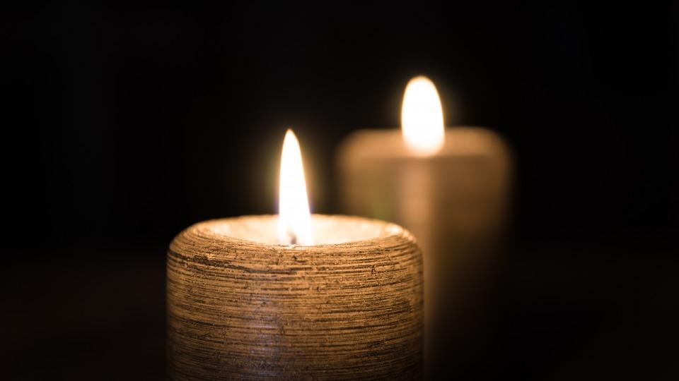 zwei helle Kerzen leuchten vor einem schwarzen Hintergrund