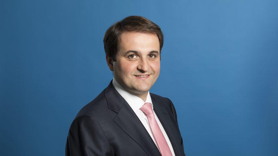 Chef der Staatskanzlei Nathanael Liminski freundlich lächelnd - Hintergrund blau.