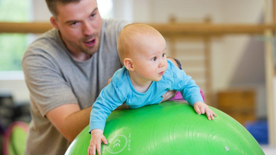 Als Bewegungsübung unterstützt ein Mann ein Baby, welches auf einem großen, grünen Ball liegt.