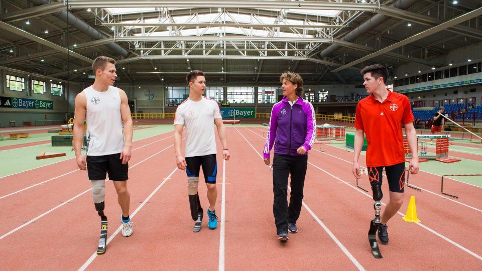 4 Sportler auf einer roten Tartanbahn. 3 von ihnen haben je eine Beinprothese.