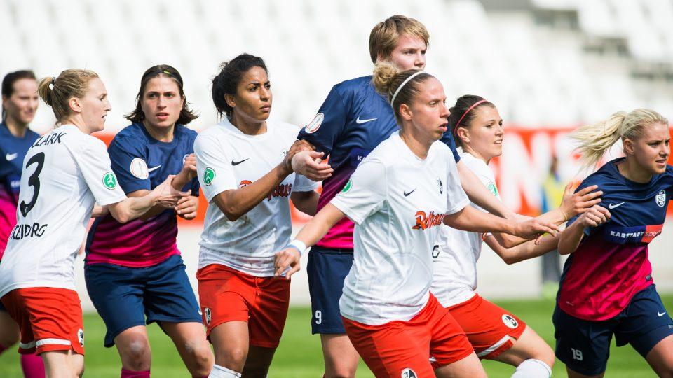 Mehrere Fußballspielerinnen in weißroten und blauroten Trikots spielen gegeneinander.