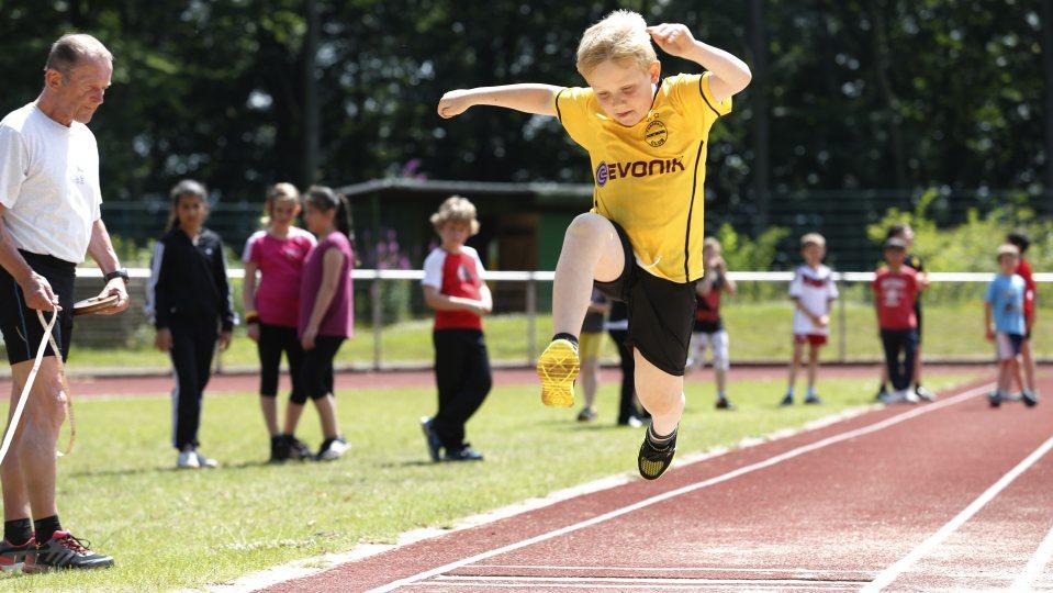 Eine Weitsprunganlage mit roter Tartanbahn. Ein Junge im gelben T-Shirt und schwarzer Hose mitten im Weitsprung. Links daneben steht ein Sportlehrer mit Maßband.