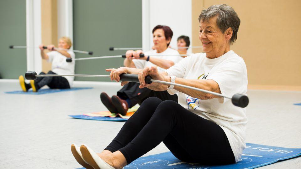 4 ältere Damen sitzen auf blauen Matten und machen Übungen.