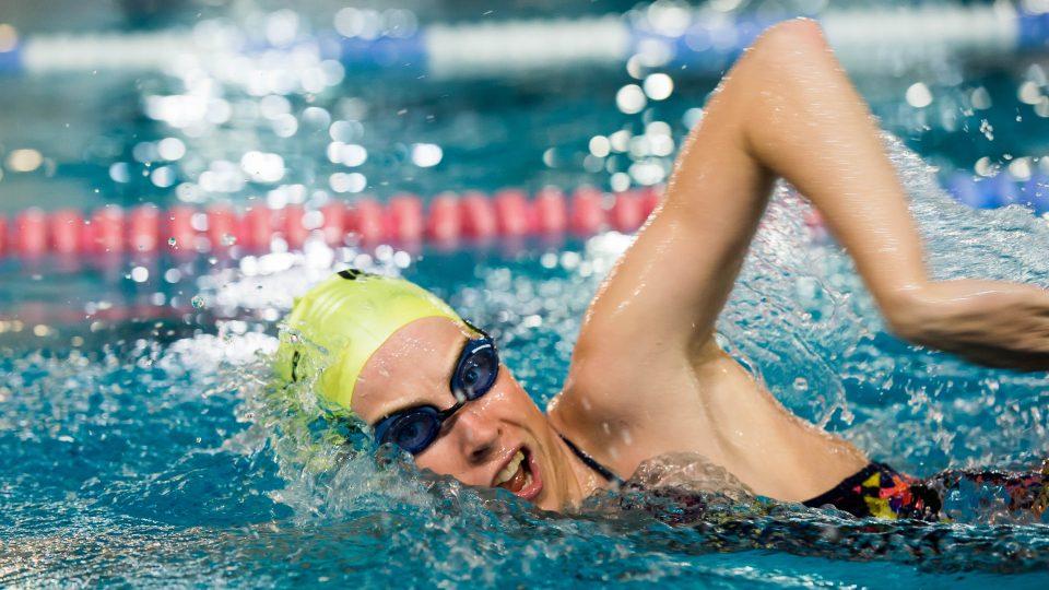 Eine Wettkampfschwimmerin im schwarzen Badeanzug mit schwarzer Schwimmbrille und  gelber Bademütze krault durchs Wasser.