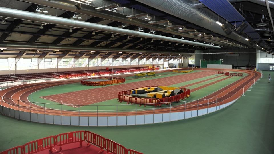 Leichtahtletiksporthalle von  innen mit einer umlaufenden, roten Tartanbahn und einer geraden, roten Tartanbahn in der Mitte. Mit weiteren Sportanlagen wie einer Hochsprunganlage. Das Dach ist geschlossen.