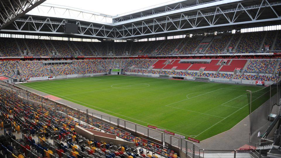 Fußballstadion mit offenen Dach kurz vor einem Spiel, die Tribünen sind größtenteils gefüllt.