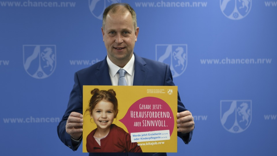 Ein Mann im Anzug steht vor einer blauen Wand und hält ein gelbes Plakat hoch, auf dem ein Kind zu sehen ist