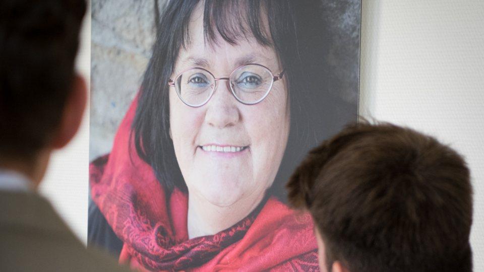 Fotoausstellung an einer Wand zeigt eine obdachlose Frau mit einem roten Schal als beeindruckenden Porträtbild.