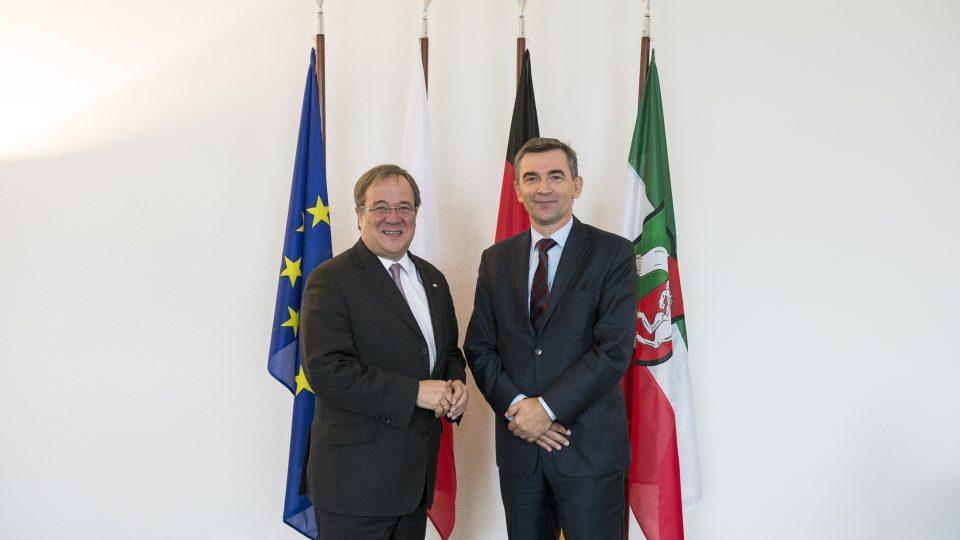Ministerpräsident Armin Laschet und der polnische Botschafter Andrzej Przyłębski, im Hintergurnd 4 verschiedene Flaggen.