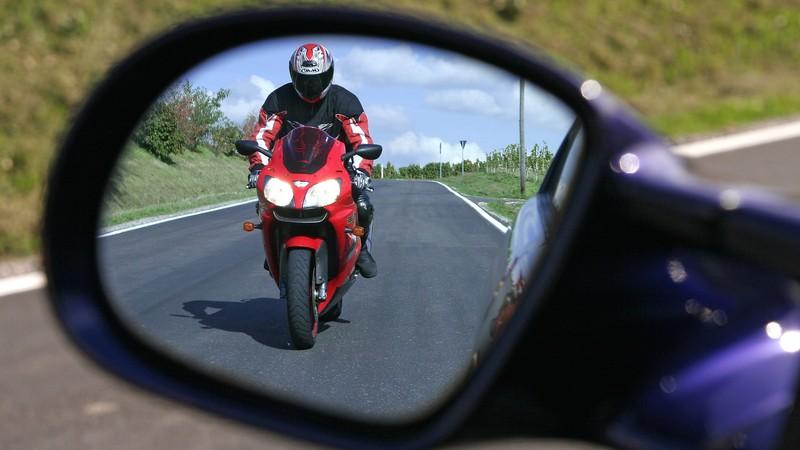 Das Bild zeigt einen Motorradfahrer im Seitenspiegel eines Autos.