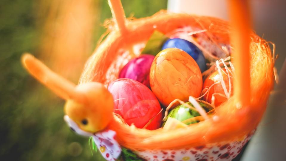 Das Foto zeigt einen Osterkorb mit bunten Ostereiern.