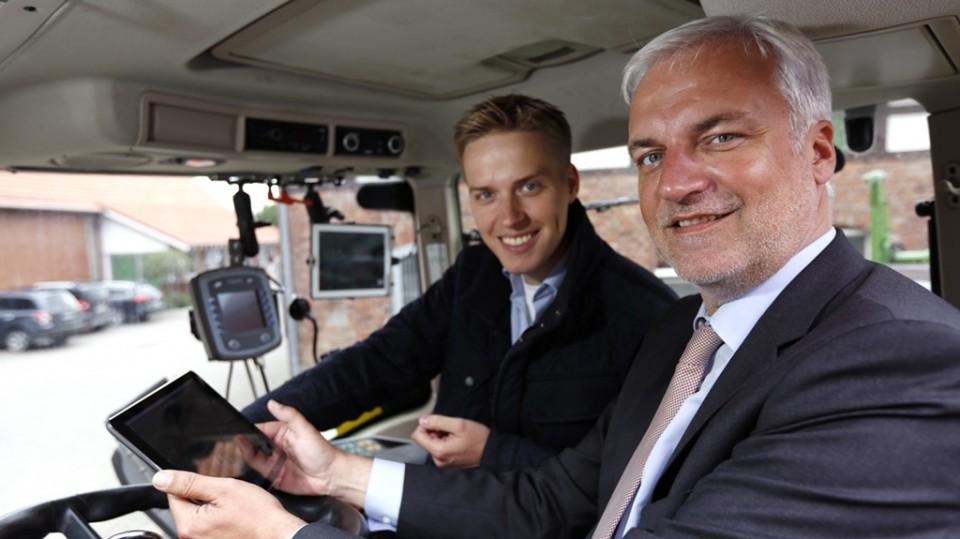 Minister Duin sitzt in einem Traktor mit einem Tablet in der Hand neben Torben Calenberg