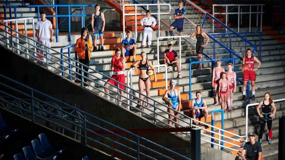 Mehrere Sportlerinnen und Sportler aus vershiedenen Sportartenstehen in ihrer Sportkleidung verteilt auf einer Tribüne. Manche haben einen Ball dabei, ganz unten steht ein Sportler mit seinem Fahrrad.
