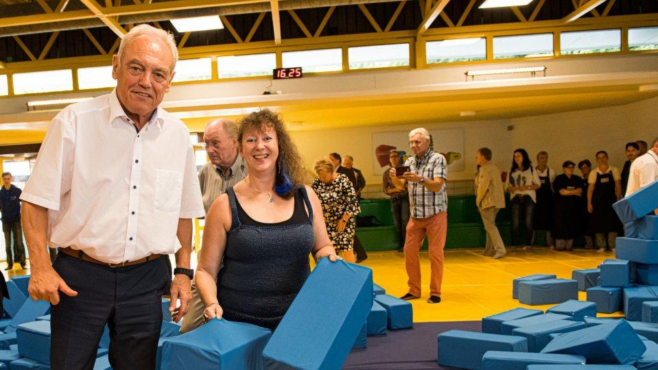 Staatssekretärin Milz mit dem Präsidenten des Landessportbundes NRW, Herrn Walter Schneeloch, an einer Schnitzelgrube gefüllt mit großen, blauen, gepolsterten Quadern.