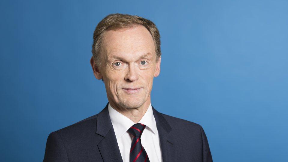 Staatssekretär Schulte vor blauem Hintergrund