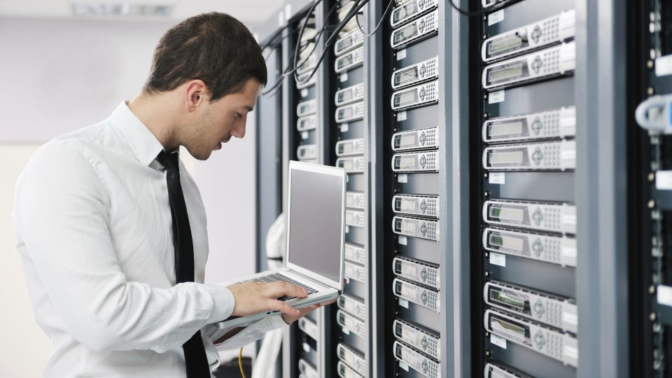 Ein Techniker in weißem Hemd und schwarzer Krawatte vor einer Wand voller Server.