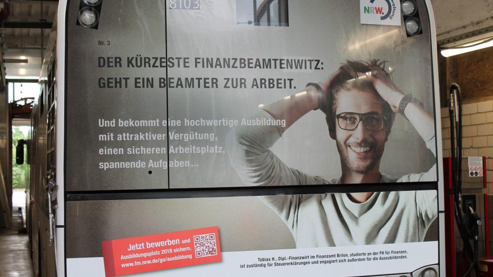 """Ein Plakat auf der gesamten Rückseite eines Buses aufgeklebt. Ein Mann mit Brille rauft sich die Haare. Links daneben der Witz: """"Geht ein Beamter zur Arbeit..."""""""
