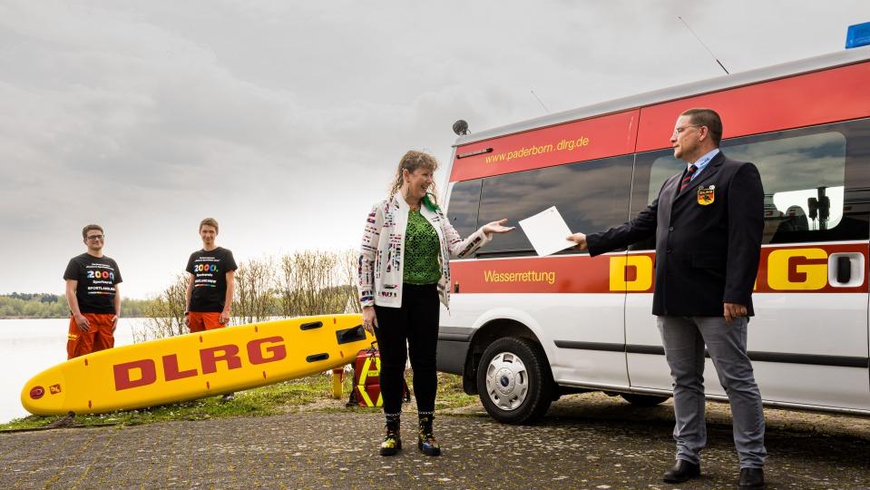 Eine Frau überreicht vor einem Rettungswagen eine Urkunde an einen Mann des DLRG