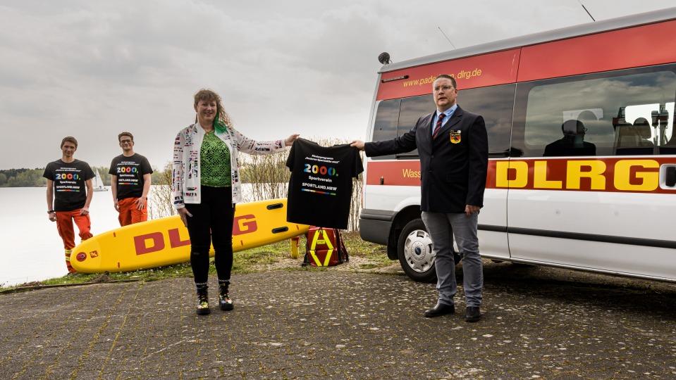 Ein Mann und eine Frau halten ein Tshirt hoch, im Hintergrund stehen zwei weitere Männer neben einem Rettungswagen