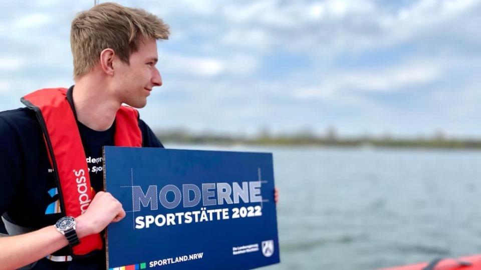 Ein junger Mann sitzt auf einem Schlauchboot und hält ein blaues Schild