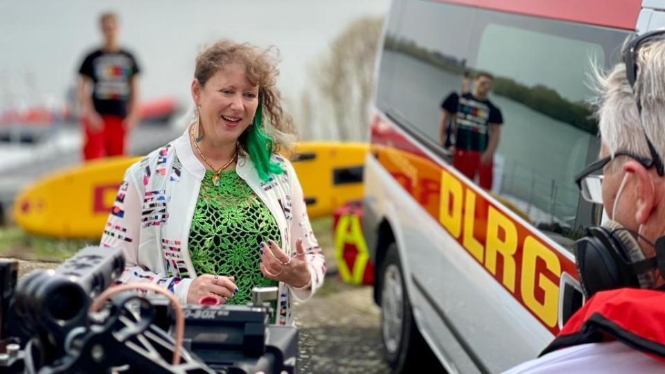 Eine Frau spricht vor einer Kamera, im Hintergrund ist ein Rettungswagen des DLRG