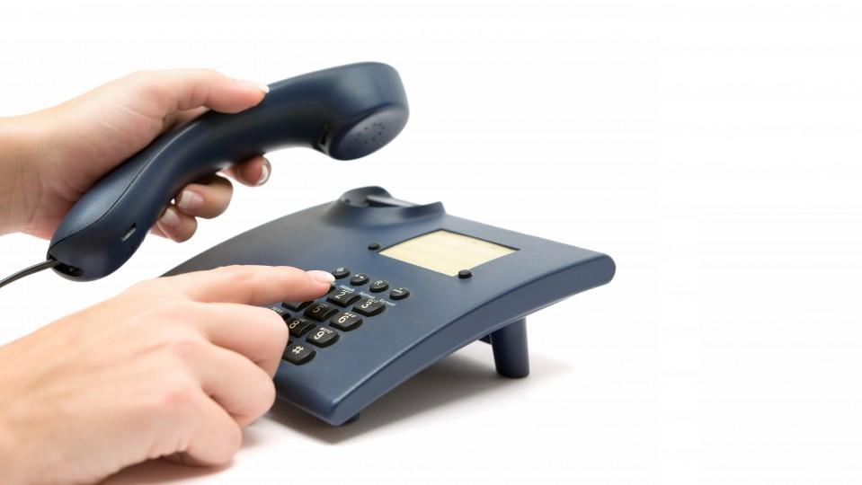 Bild zeigt eine Hand, die die Tatstatur eiens Telefons bedient