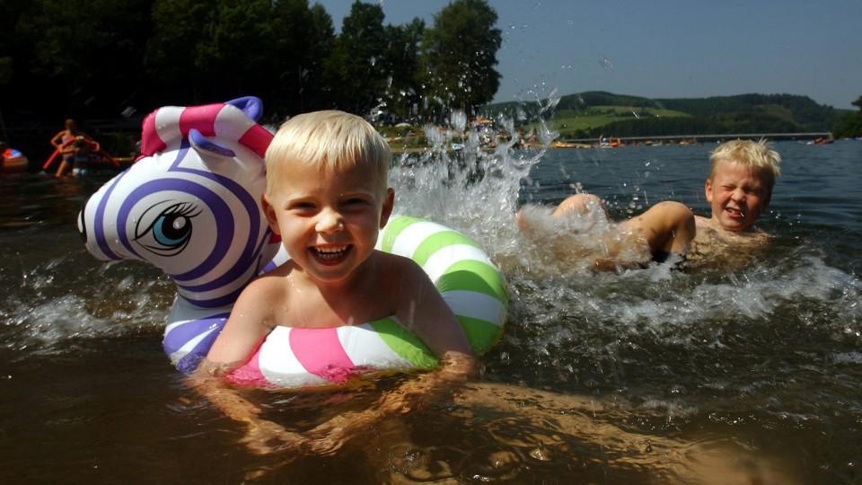 Das Foto zeigt 2 Kinder, die im See baden und sich freuen.