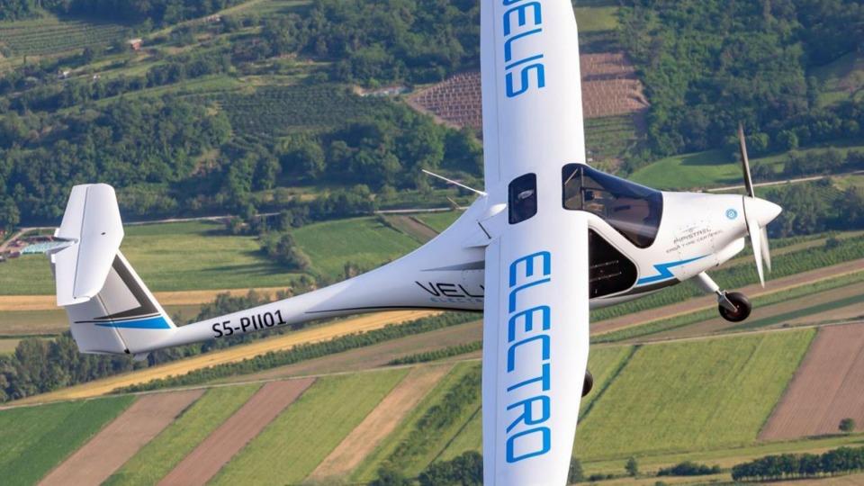 Ein weißes Flugzeug fliegt hoch über einigen Feldern