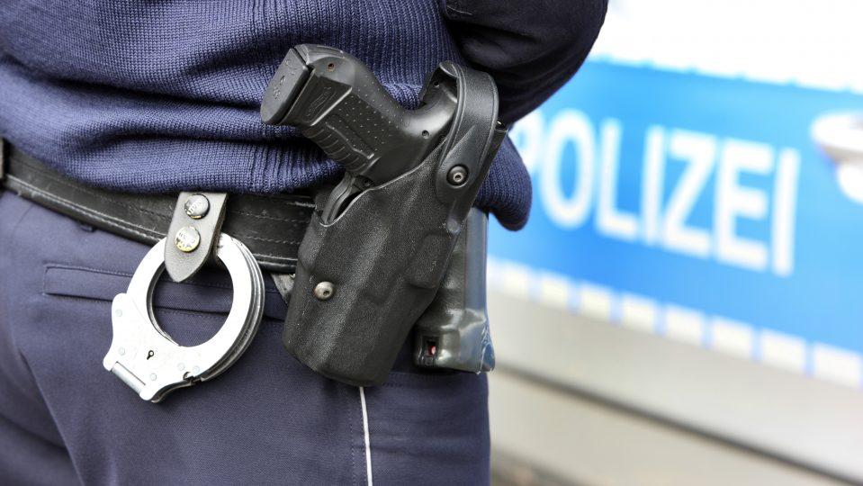 Polizist mit Waffe vor Polizeiwagen